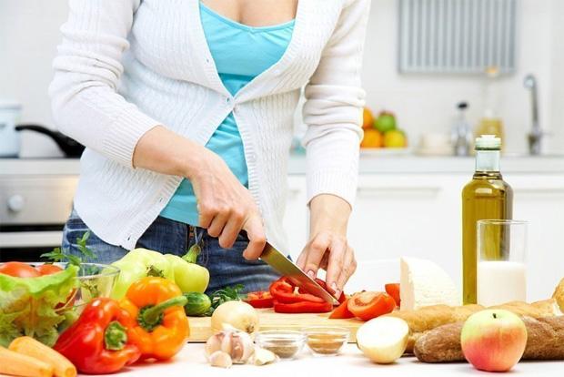 Девушка в белой кофточке готовит на кухне и нарезает перец большим ножом