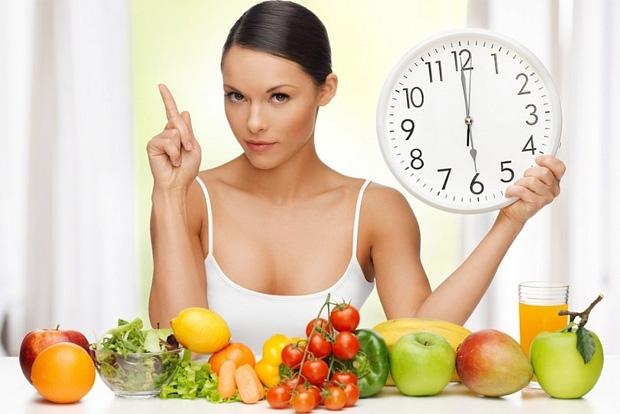 На фоне полезных фруктов сидит девушка и держит большие настенные часы в руке