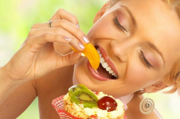Счастливая девушка с удовольствием ест свежие экзотические фрукты из миски