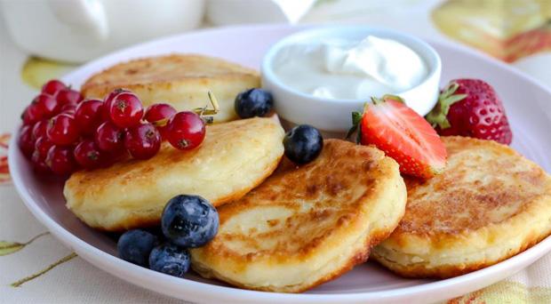 В белой тарелке лежит несколько сырников, креманка со сметаной и немного свежих ягод