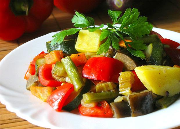 На столе в белой тарелке выложены тушеные овощи с зеленью и приправами