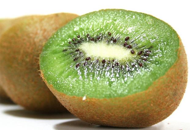 На столе лежит спелый киви в разрезе и еще один целый фрукт