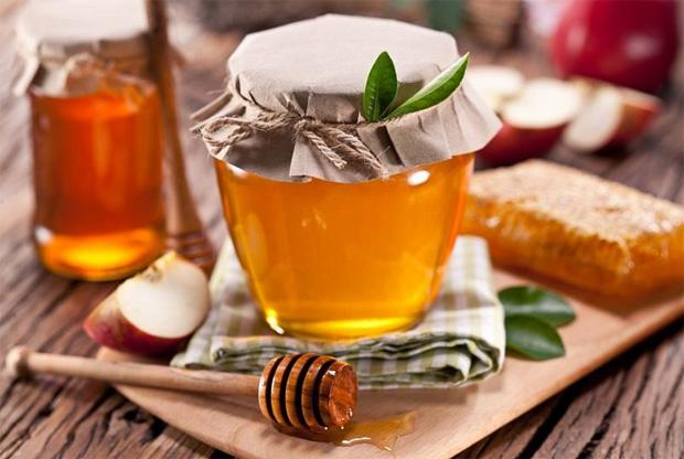 На столе стоит баночка с медом и тряпичной крышкой и палочка для него