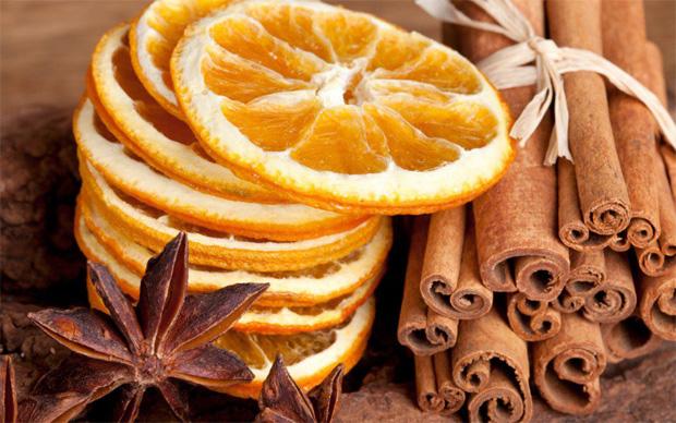 На столе высушенные апельсиновые кольца и несколько трубочек корицы