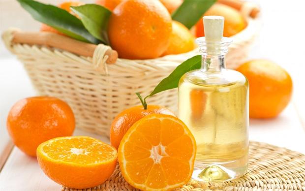 На столе корзина с апельсинами и разрезанные плоды с бутылкой апельсинового масла