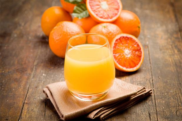 На деревянном столе несколько апельсинов и стакан с апельсиновым соком