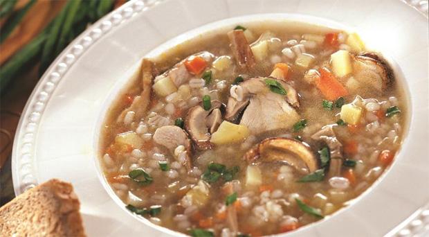 В праздничной глубокой тарелке вкусный грибной суп с перловой крупой