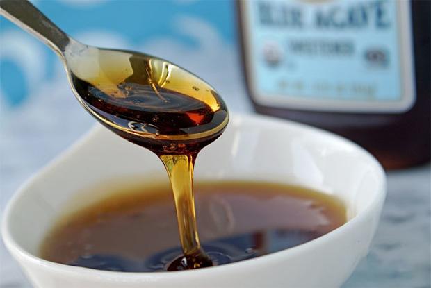 Чайной ложкой выливают в белую чашку густой сироп из топинамбура