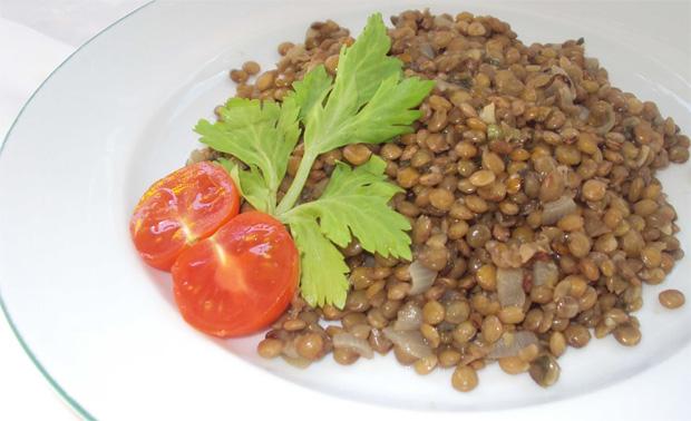 В белой тарелке чечевичная каша, украшенная помидорами черри