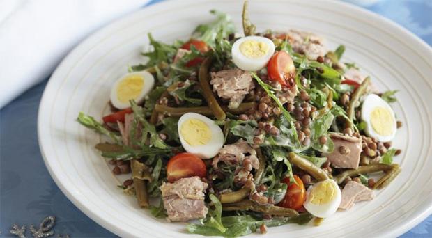 На большой белой тарелке салат из чечевицы, стручков фасоли и овощей