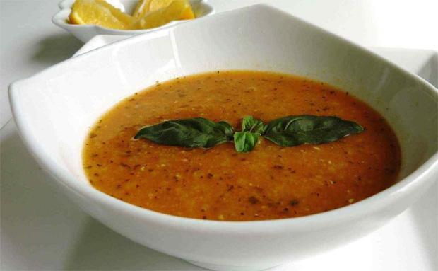 В глубоком белом блюде суп из чечевицы, украшенный листочками зелени