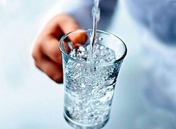 Мужчина держит прозрачный стакан с ручкой и наливает в него минеральную воду