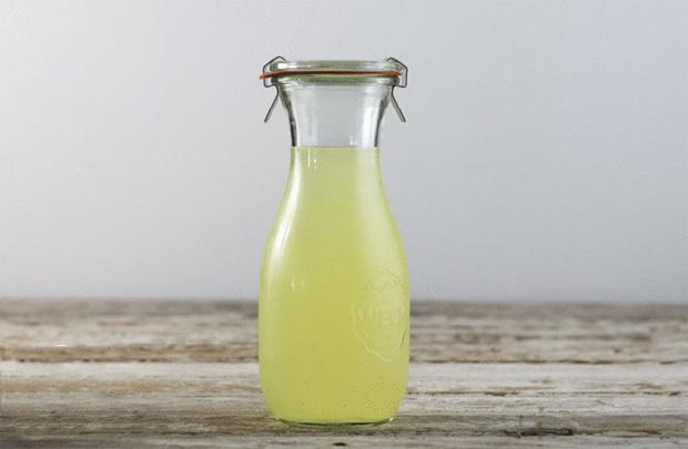 На постом столе на фоне голубой стены стоит бутылка с молочной сывороткой