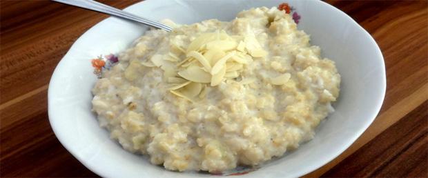 В белой тарелке с ложкой овсяная каша с добавление отрубей и зеленого яблока