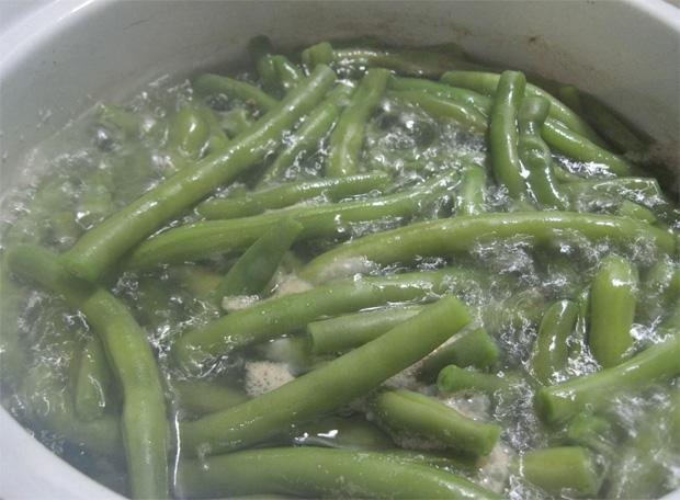В кастрюле на плите завариваются зеленые створки фасоли