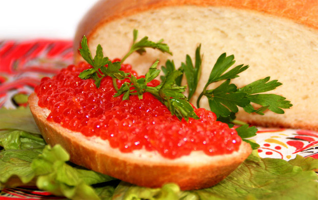 На столе буханка белого хлеба и бутерброд с красной икрой на листе салата