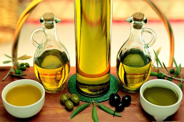На столе две бутылочки и две мисочки из масла оливок и маслин
