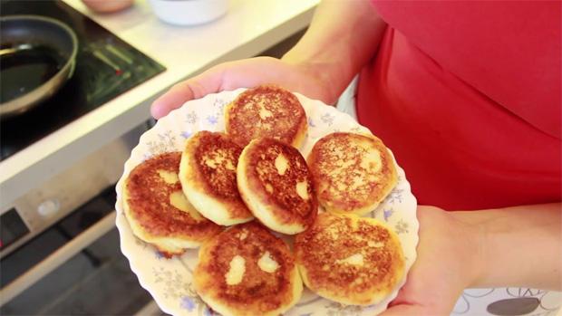 Девушка держит в руках блюдо с готовыми ароматными сырниками