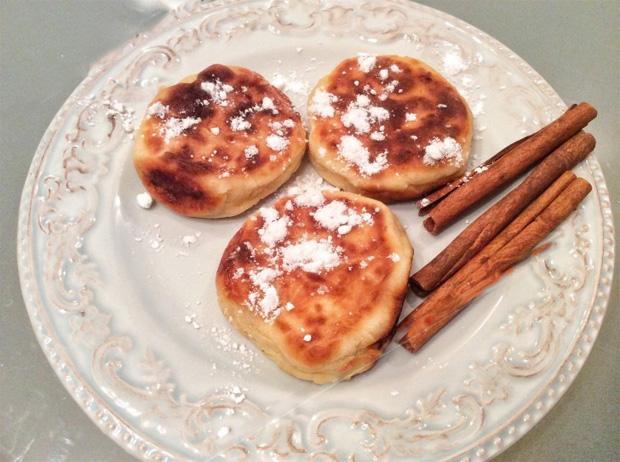 На белом блюде лежат приготовленные сырники с пудрой и корицей