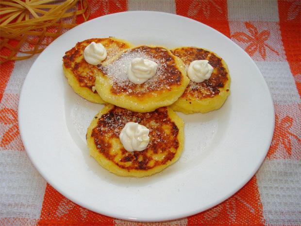 На белой тарелке лежит несколько сырников с сахарозаменителем и сметаной