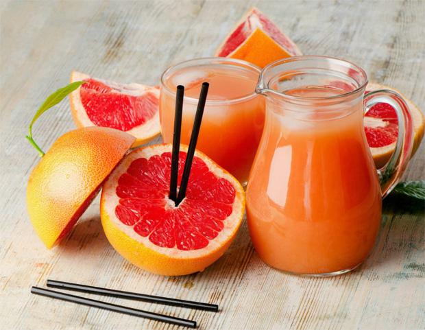 На столе разрезанный грейпфрут с трубочками в сердцевине и кувшин с соком