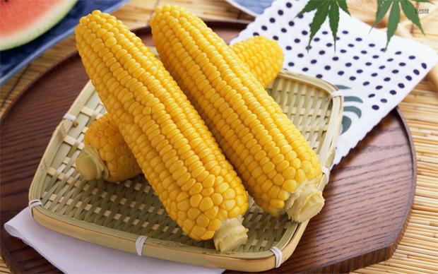 На плетеном блюде лежит три початка вареной кукурузы