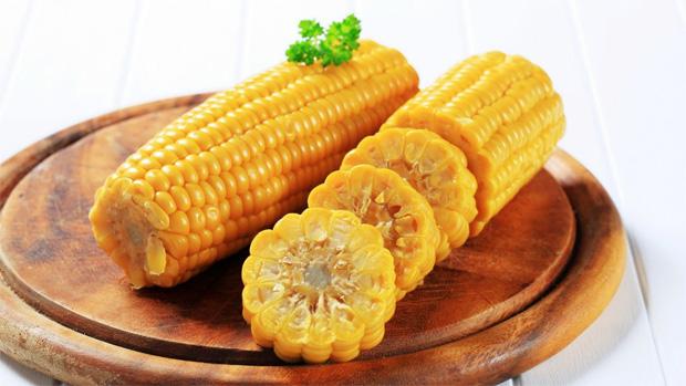 На деревянной подставке лежит два початка вареной кукурузы с нарезкой
