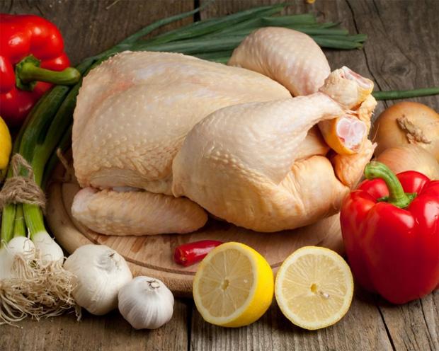 На столе среди овощей и приправ лежит тушка птицы для приготовления