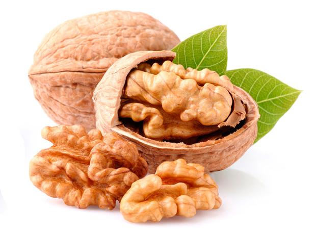 На столе один целый и один расколотый грецкий орех, вынутое ядро и листики