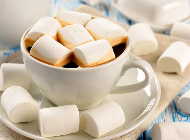 На столе стоит белая чашка с блюдцем и кофе, рядом и в ней находится зефир