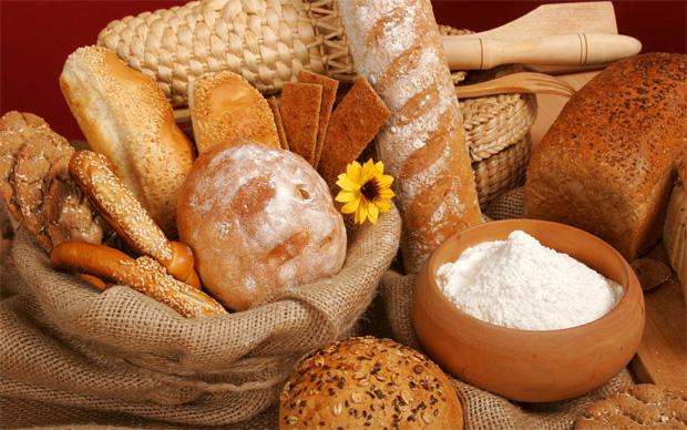 На столе большое разнообразие хлебобулочных изделий и миска с солью