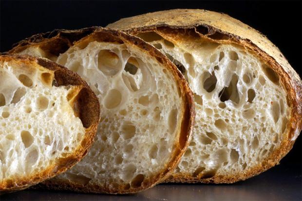 На черном фоне нарезанный пушистый домашний хлеб с хрустящей корочкой