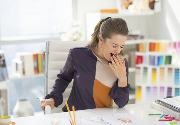 Девушка сильно зевает на своем рабочем месте в офисе