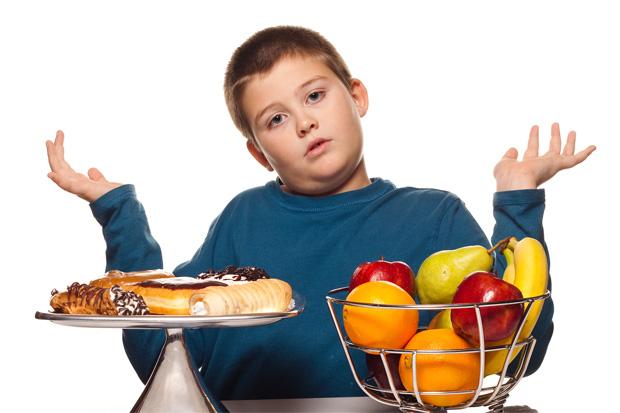 Полный мальчик подросток разводит руками при выборе сладостей или фрктов