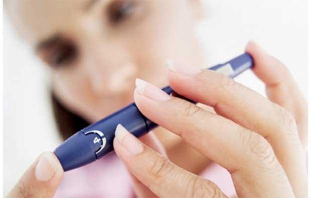 Женщина после 40 лет измеряет уровень сахара в крови делая прокол на пальце