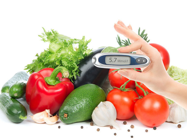 На фоне свежих спелых овощей женщина держит прибор для измерения сахара в крови
