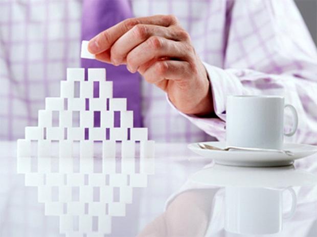 Мужчина в клетчатой рубашке за столом строит горку из кубиков сахара и рядом стоит чашка