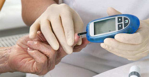 Врач измеряет пациенту уровень глюкозы в крови специальным прибором