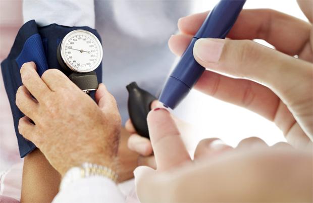 Человек делает прокол на пальце ручкой с иглой и мерит артериальное давление