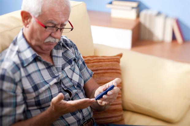 Пожилой мужчина с седыми усами и в очках измеряет прибором уровень сахара в крови