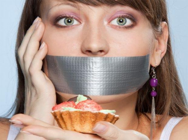 Девушка с металлическим скотчем на лице держит пирожное в руках