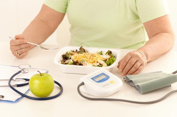 Человек ест за столом, на котором стетоскоп, тонометр и зеленое яблоко