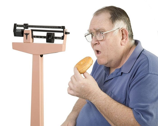 Мужчина с лишним весом кушает пончик на фоне медицинских весов