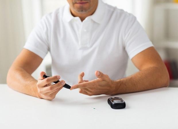 Мужчина в белой футболке сидит за столом и берет кровь из пальца на анализ
