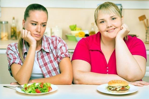 Две девушки сидят за столом с едой и худая смотрит на гамбургер у полной