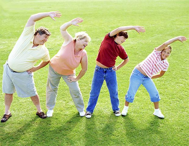 Счастливая семья из четырех человек выполняет физические упражнения на природе
